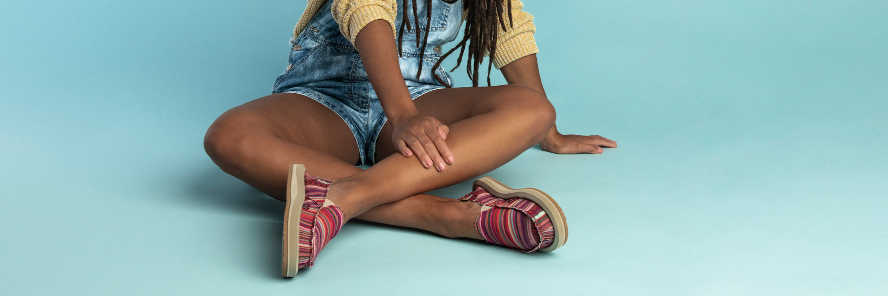 Close up of a person's legs wearing Sanuk Shoes.