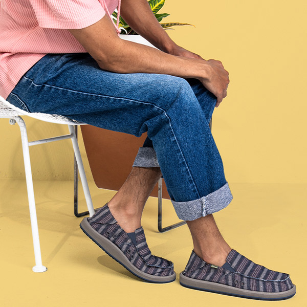 Close up of someone, wearing Sanuk shoes, sitting in a chair.