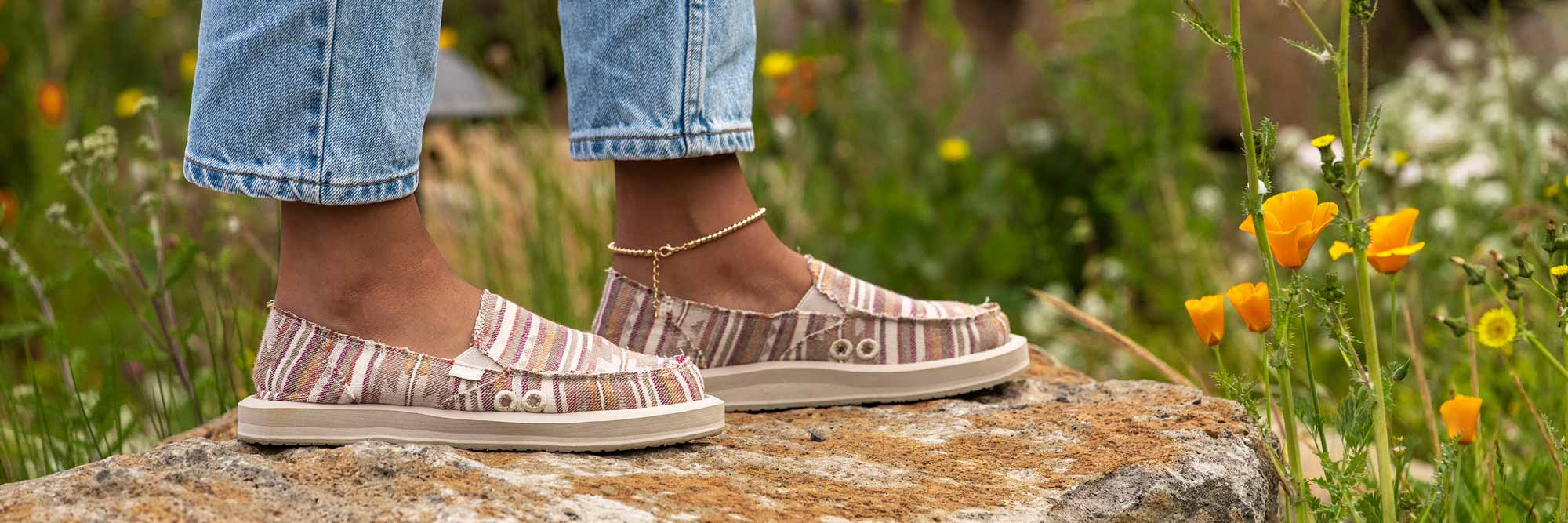 Close up of a woman's feet wearing Sanuk Sidewalk Surfers, with rock and grass in the background.