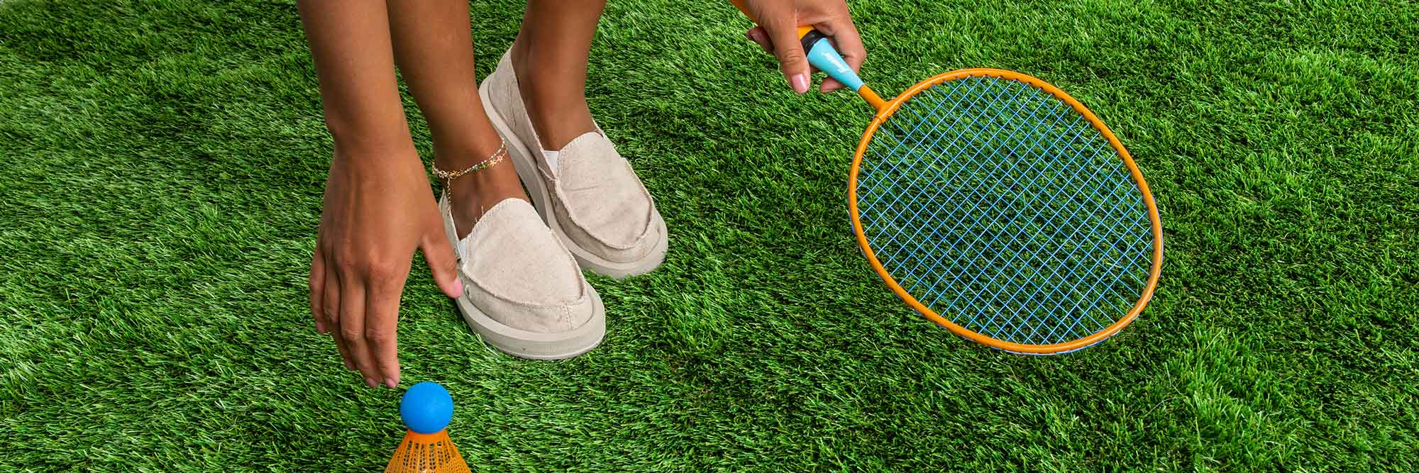 Close up of a woman's feet wearing Sanuk shoes and holding a racket.